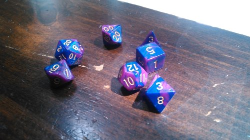 Some truly beautiful pinkish purplish dice with gold lettering lie on the table, waiting to be rolled against a Bugbear.